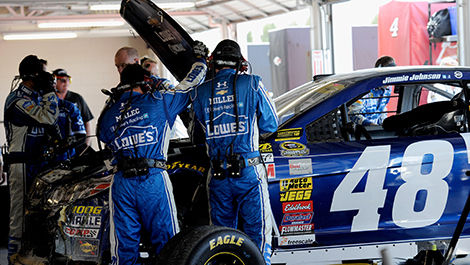 Crew members for Jimmie Johnson, driver of the No. 48 Lowe's Chevrolet, work on the car after the crash.
